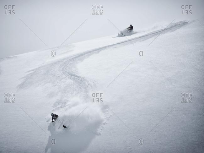 April 29, 2012: Men riding snowmobiles down snowy mountain