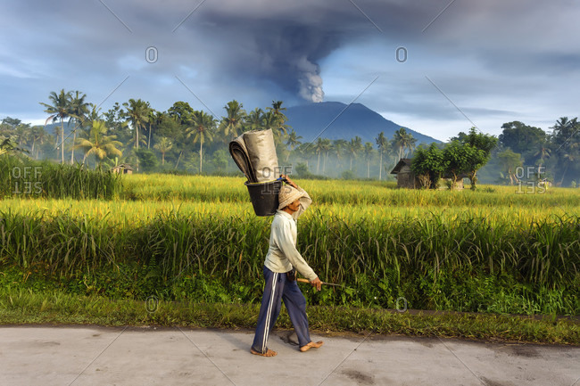 November 27, 2017: Man walking on a road and volcano Agung in background, Bali, Indonesia