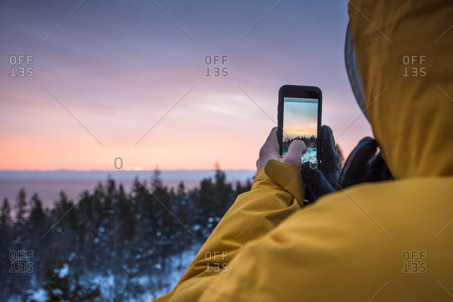 Man taking picture with smartphone, Acadia National Park, Maine, USA