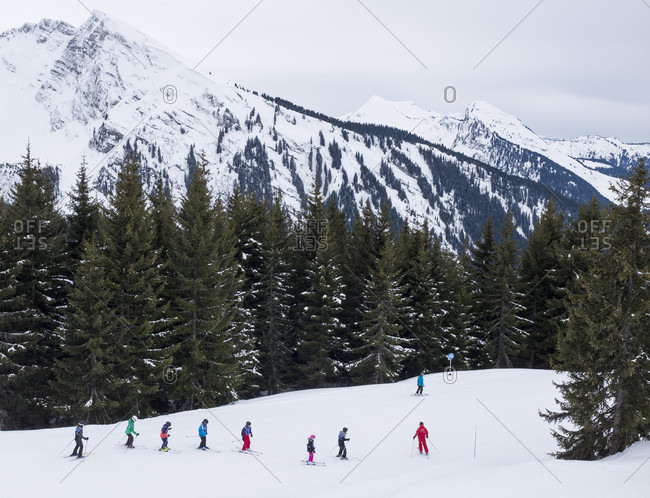 Ski school students following ski instructor down slope at Morzine Ski Resort, Portes du Soleil, Haute-Savoie, France