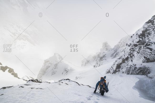 Mountain climber climbing up mountain in winter, Tatra Mountains, Slovakia