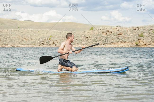 Man paddleboarding in lake, Blue Mesa Reservoir, Colorado, USA