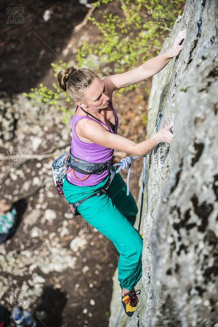 Woman rock climbing up cliff, Jura, Olkusz, Malopolskie Province, Poland