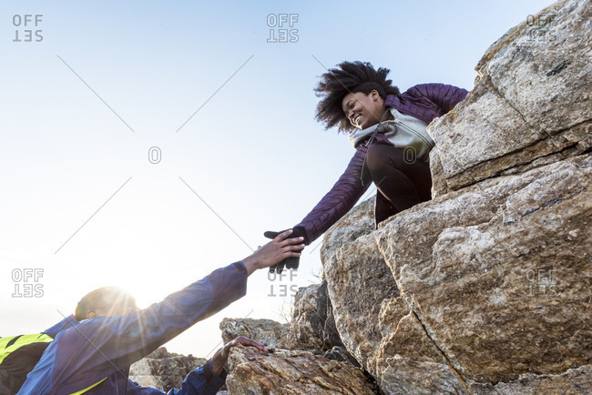 Woman helping man up rock outcrop, Kittery, Maine, USA