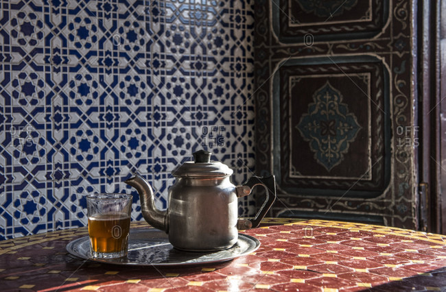 Mint tea in glass and tea pot on table, Marrakesh, Morocco