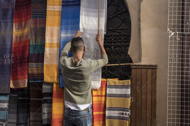 Man hanging shawls for sale in the medina of Fes, Morocco