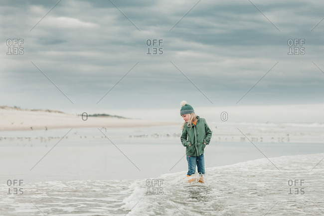 Young girl walking in water on beach