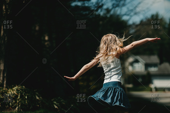 Young blonde girl twirling outside