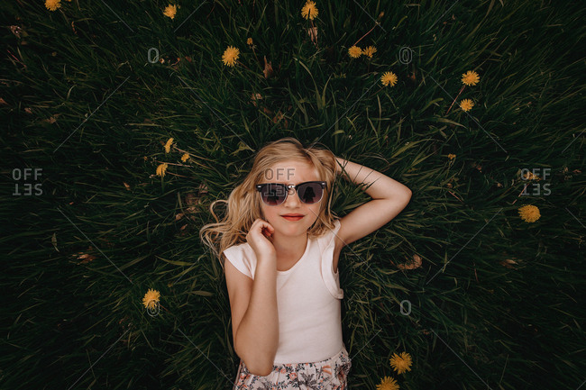 Young blonde girl wearing sunglasses lying in grass with dandelions