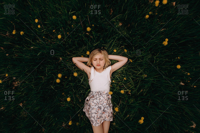 Young blonde girl lying in grass with dandelions