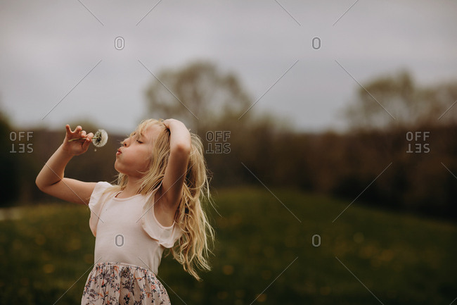 Blonde girl blowing seeds from a dandelion