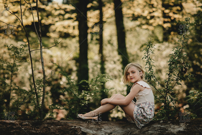 Young blonde girl sitting on log in a forest