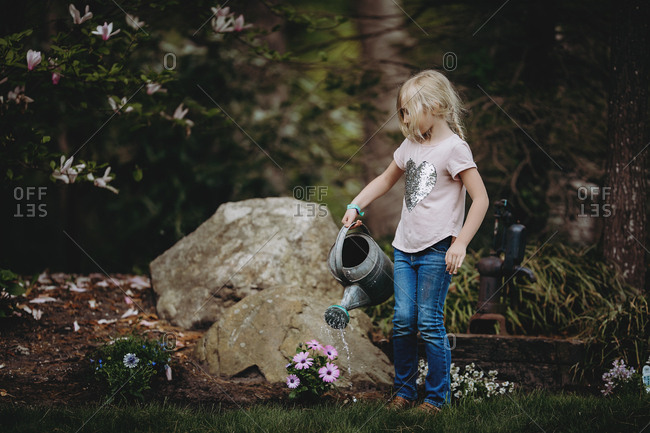 Blonde girl watering flowers in her backyard