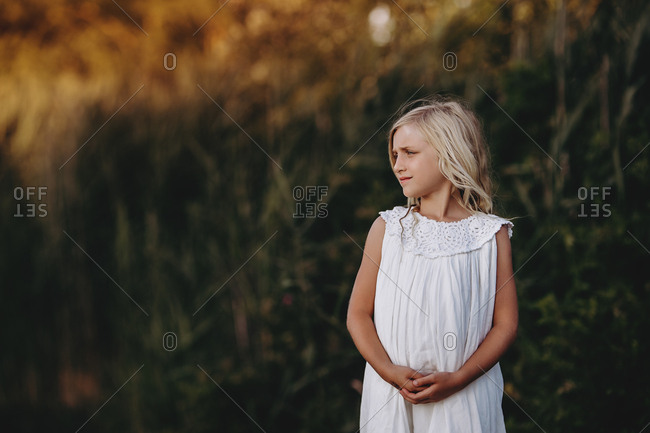Portrait of a young blonde girl in a field at sunset
