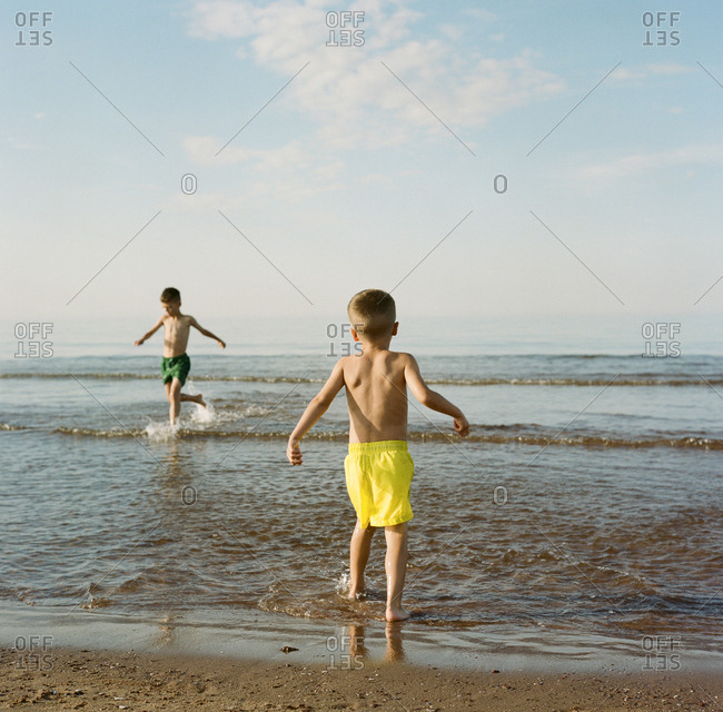 Two young boys playing in water at a beach
