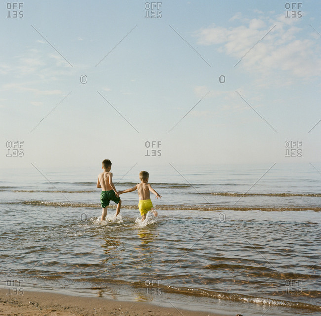 Rear view of two young boys playing in water at a beach