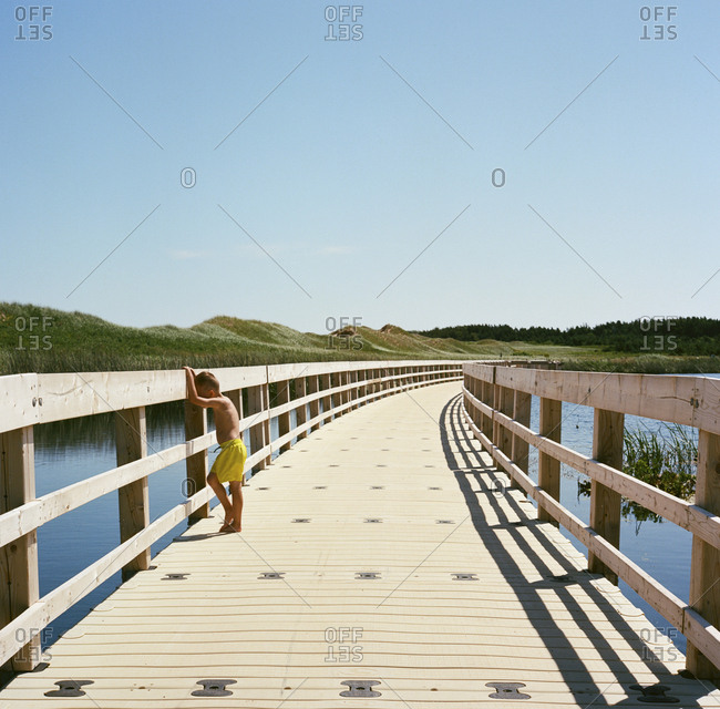Blonde boy looking at water from boardwalk