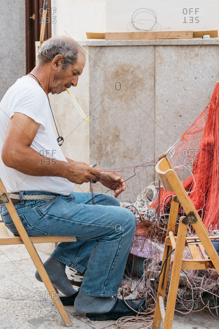 Marettimo, Italy - August 1, 2018: Fisherman untangling nets