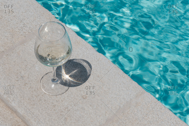 Wine glass beside a pool