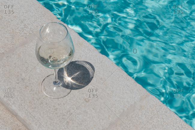 Wine glass beside a pool