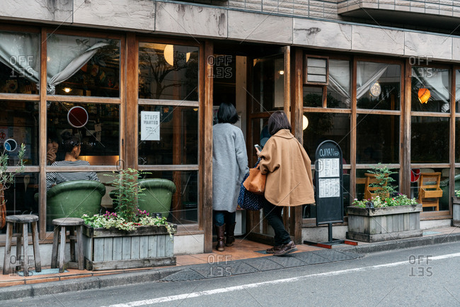 Tokyo, Japan - November 4, 2016: Two women walking into coffee shop