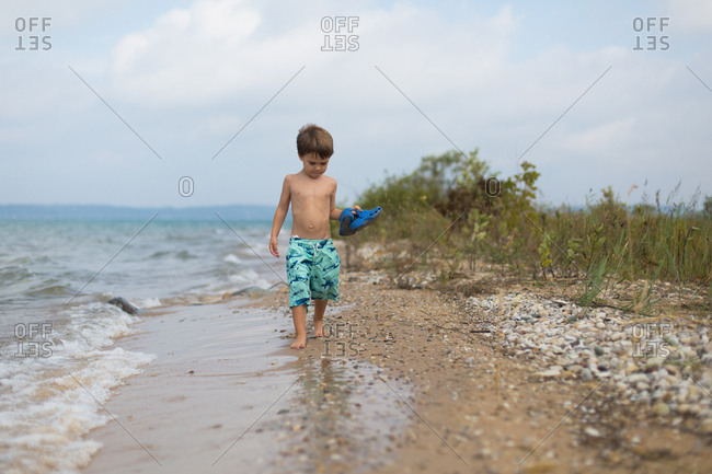 Boy holding his shoes as he walks along the beach