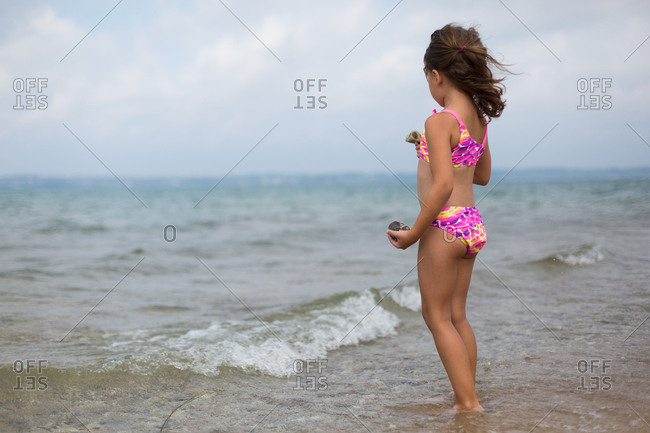 Girl wading in ocean waves holding rocks she found on the beach