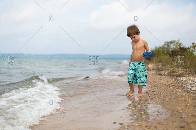 Boy holding his shoes and sticking his toes in the water at the beach