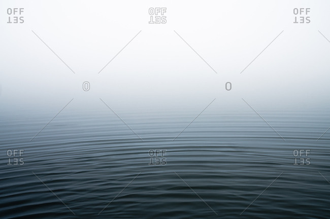 Ripples in water on lake on foggy morning