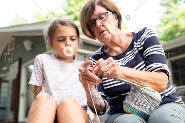 Grandmother demonstrating to granddaughter how to knit