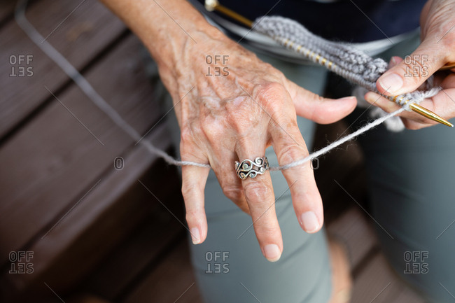 Senior woman threading yarn through fingers while demonstrating how to knit