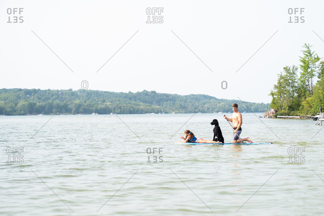 Father with his daughter and their pet dog on a paddleboard on a lake