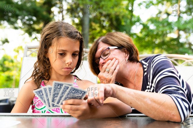Grandmother teaching granddaughter how to play a card game