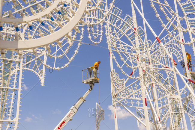 "July 1, 2015: Italy, Apulia, Galatina . Men on crane with elevator basket mounting traditional lights called ""luminarie"" for San Pietro e Paolo festivity"