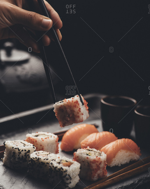 Eating sushi rolls with salmon and tuna fish.