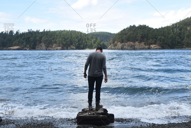 Man standing on rock looking down at ocean waves on the beach