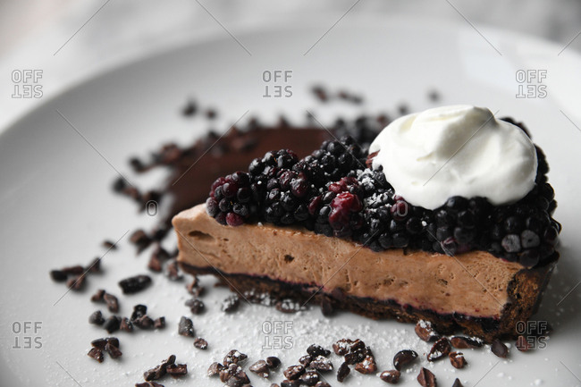 Chocolate cream pie topped with fresh blackberries, cacao nibs, and whipped cream