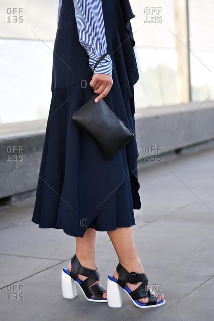 Stylish Woman Wearing Chunky Heels, Flowing Garment, Clutch Bag, Vertical