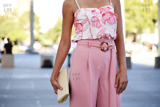 Elegant Woman Wearing Pastel Pink Outfit, Holding Natural Clutch Bag, Midsection