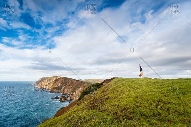 Woman does a headstand on a seacliff in Point Reyes California