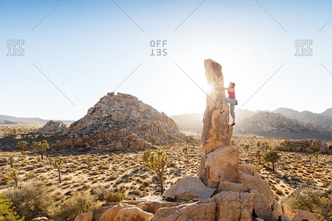 Woman climbs up a desert spire in Joshua Tree National Park California