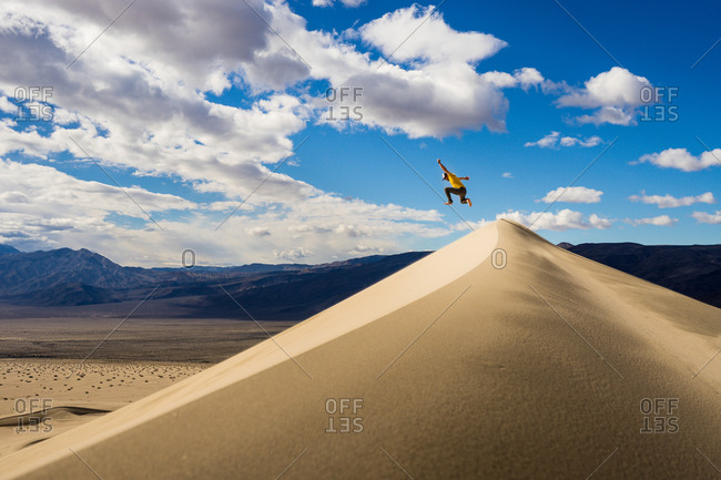 Man jumps off the top of a sand dune in Death Valley National Park California