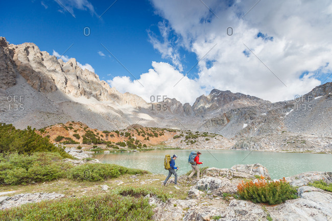 Couple hikes along the shore of an alpine lake in the Sierra Nevada Mountains of California