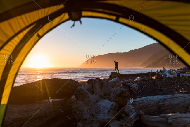 Man explores the beach on a backpacking trip on the loast coast of Northern California