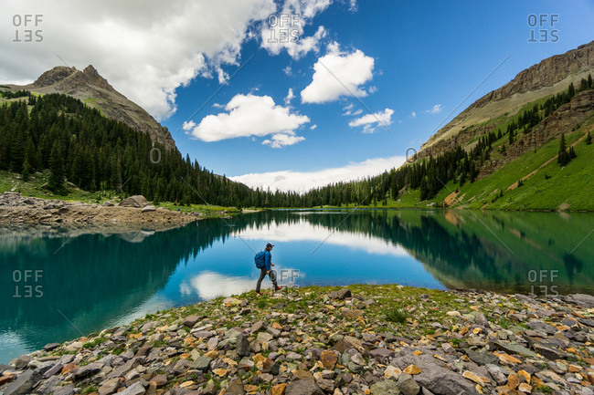 Man hikes along the shore of blue lake with reflection in the San Juan Mountains of Colorado