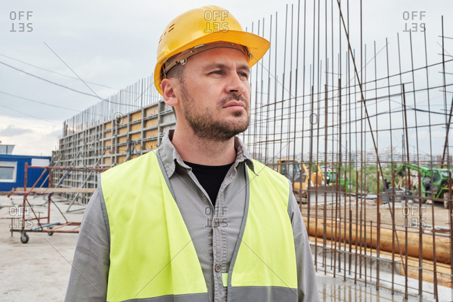 Portrait of confident Caucasian male contactor in safety helmet standing at building site and looking into the distance thoughtfully