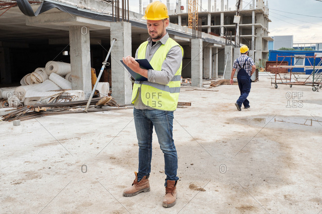 Confident Caucasian male contractor in safety helmet standing at building site with clipboard and conducting quality control