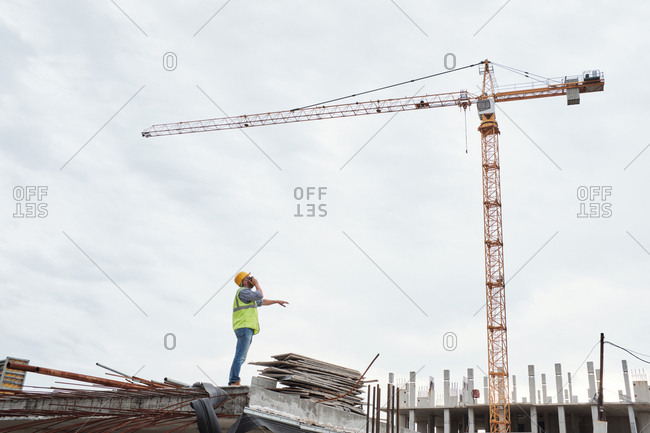 Low angle view of unrecognizable foreman talking on portable transmitter while controlling work of tower crane at building site
