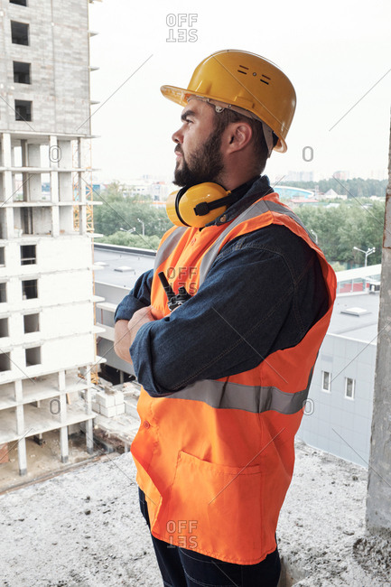 Side view of bearded male engineer in safety helmet standing on project site with crossed hands and watching building process