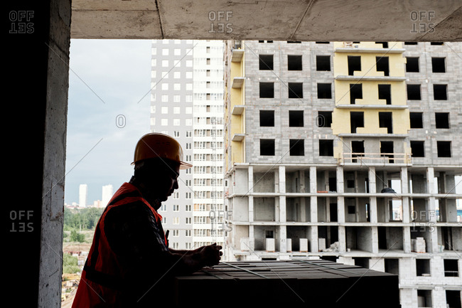 Side view of male contractor in safety helmet standing on project site, leaning on concrete blocks and contemplating, incomplete apartment buildings in the background